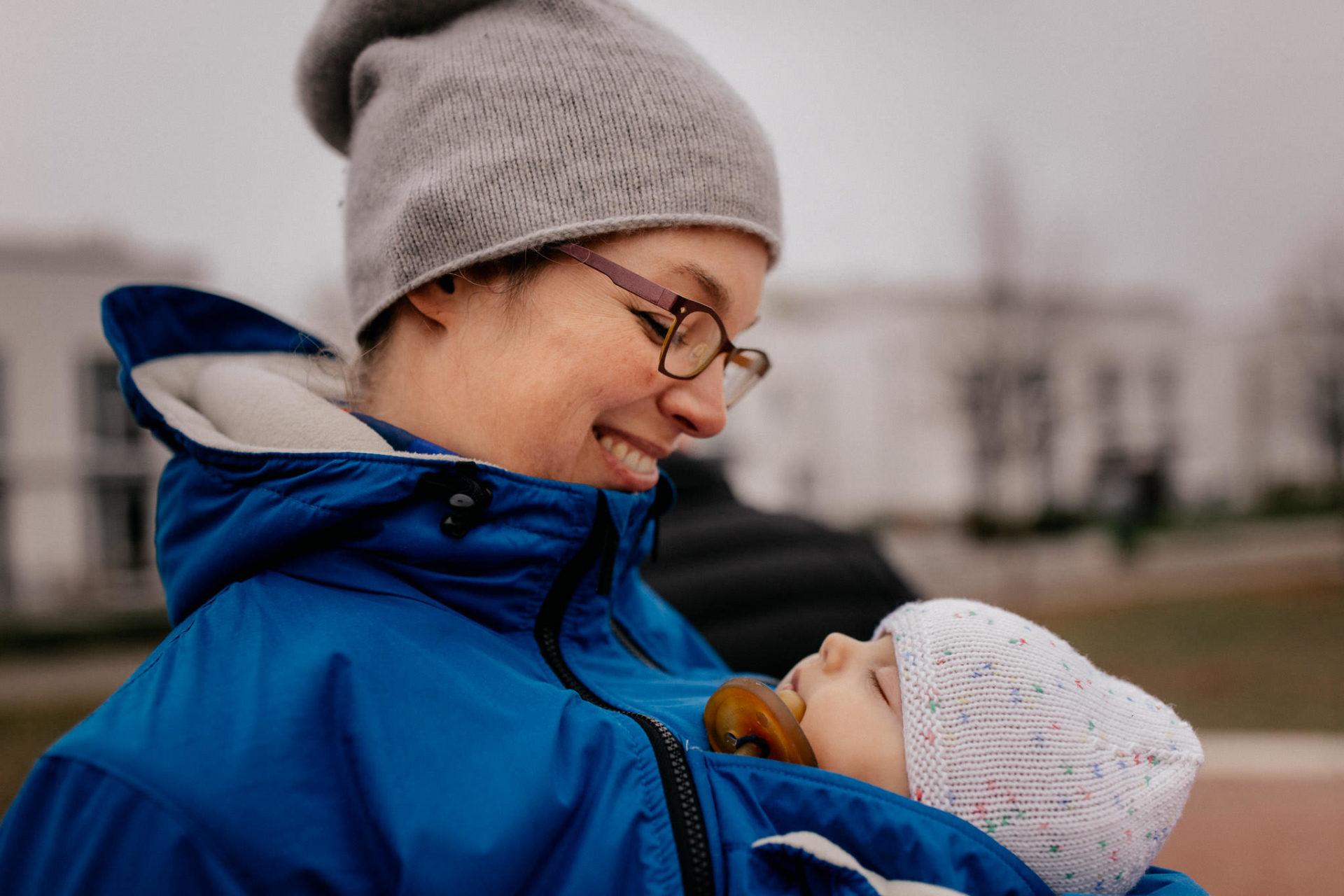 familienfotografie-mainz-journalistische-kinderbilder-familienspaziergang-mama-und-baby-in-babytrage-winter-muetze