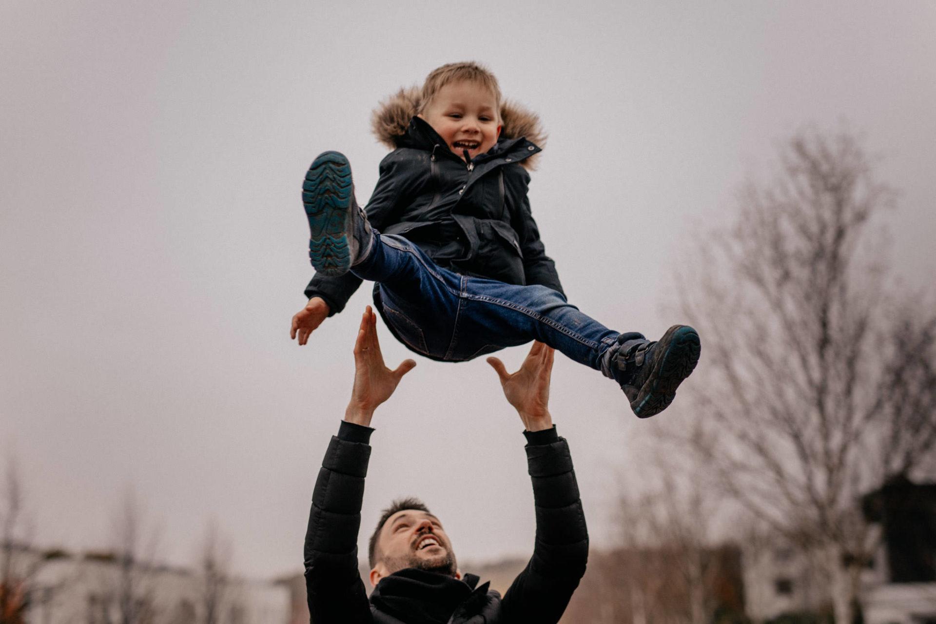 familienfotografie-mainz-journalistische-kinderbilder-familienspaziergang-papa-und-sohn-in-der-luft-spielen