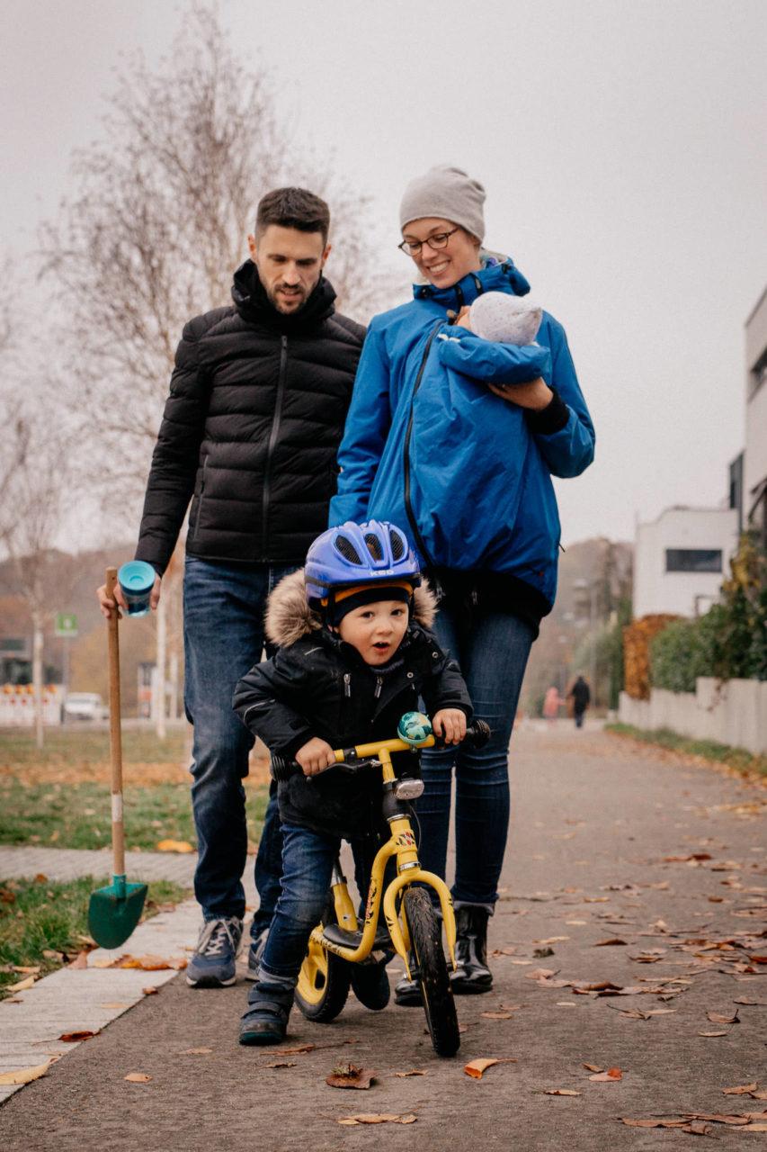 familienfotografie-mainz-journalistische-kinderbilder-familienspaziergang-zu-viert-laufrad-babytrage-junge-eltern