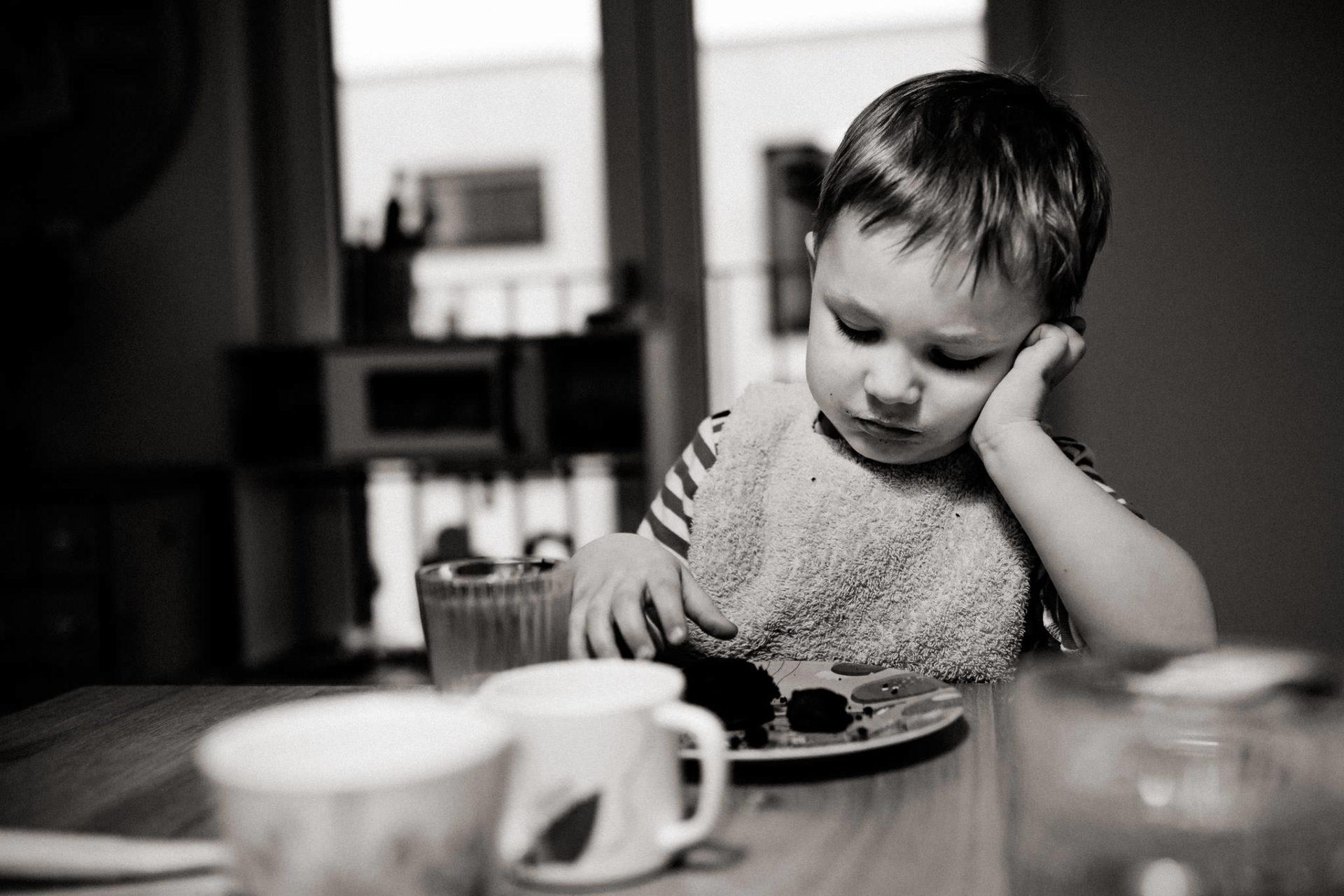familienfotografie-mainz-journalistische-kinderbilder-dreijaehriger-isst-cookie-schwarzweiß