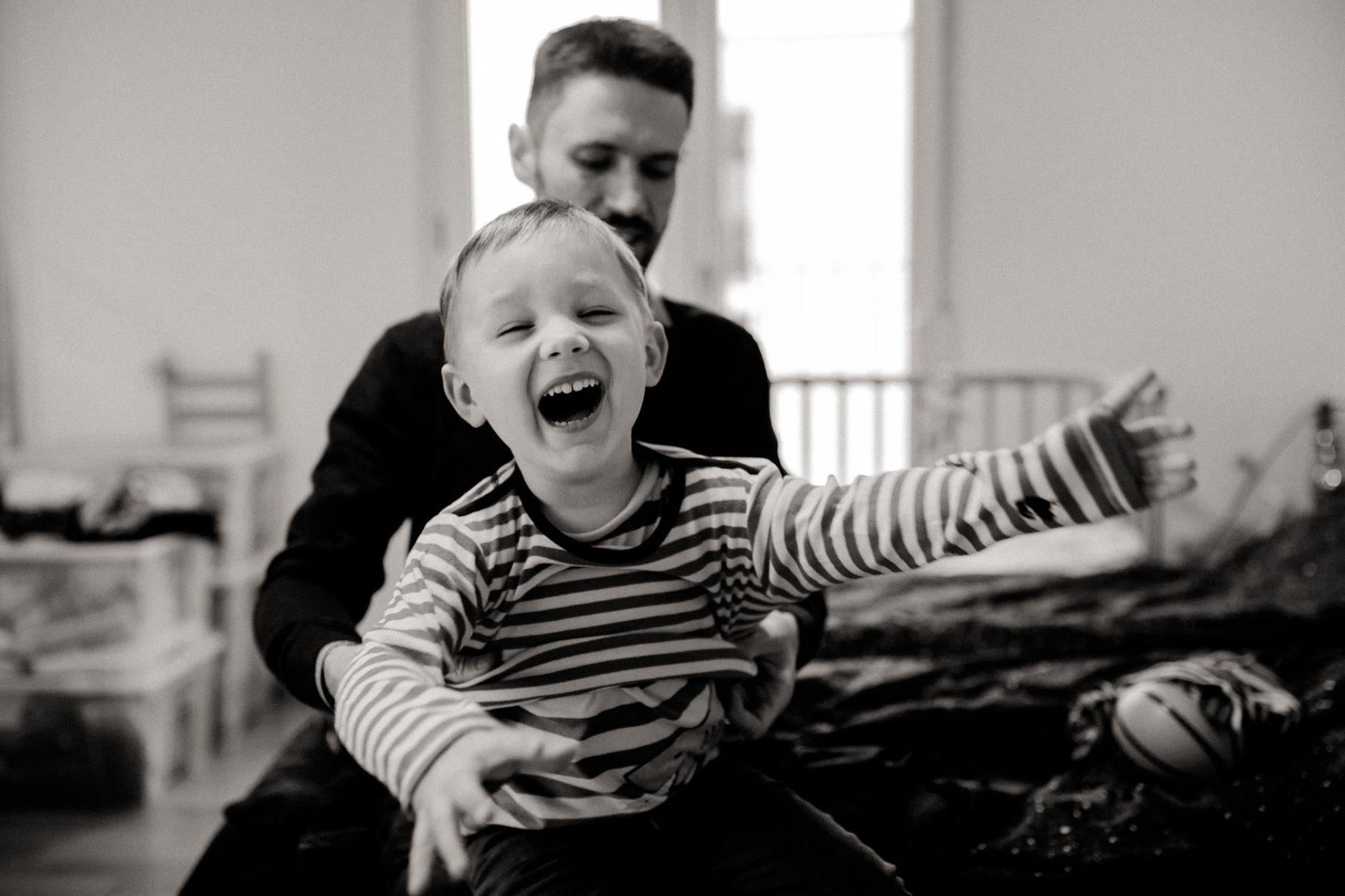 familienfotografie-mainz-journalistische-kinderbilder-papa-zieht-sohn-um-froehliches-lachen-schwarzweiss