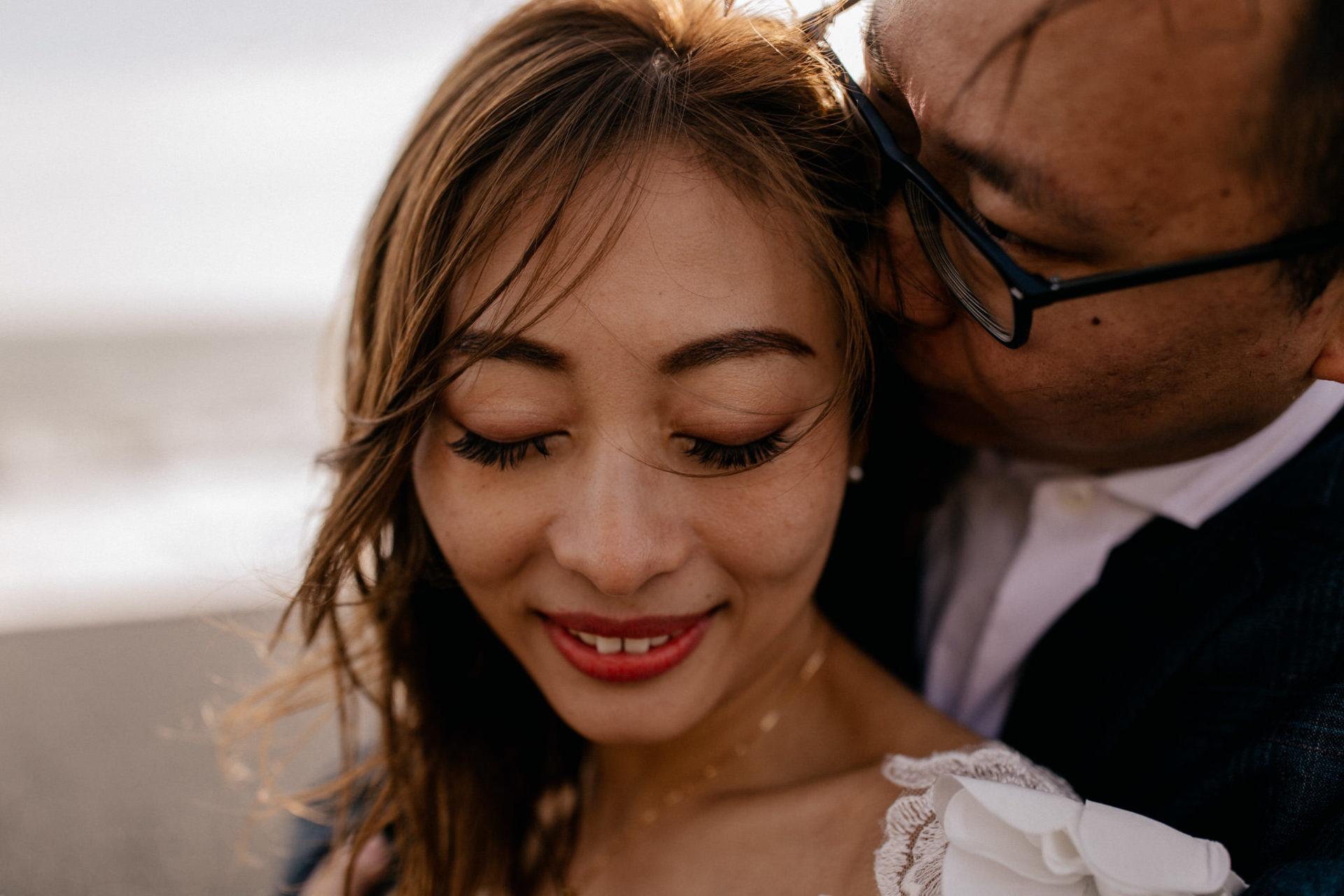 Verlobungsfotos-Island-Abeuteuer-Foto-Session-Nahaufnahme-Paar-Am-Schwarzen-Strand-Wind-in-Haaren